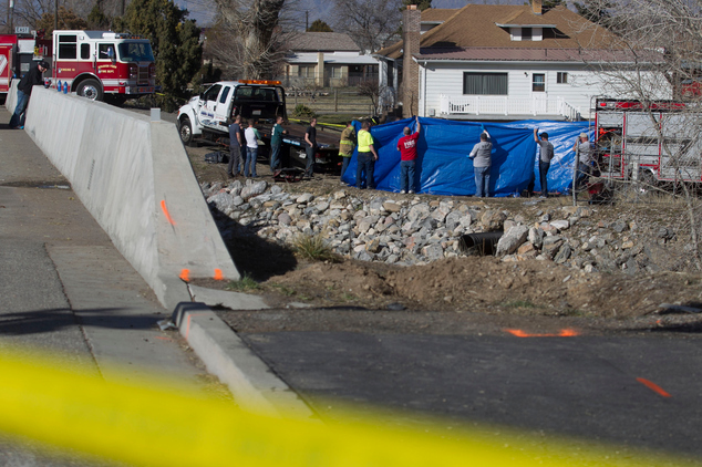 In this March 7, 2015 photo, officials respond to a report of car in the Spanish Fork River near the Main Street and the Arrowhead Trail Road junction in Spanish Fork, Utah. An 18-month-old girl survived a car crash in a frigid Utah river after being strapped in a car seat upside-down for some 14 hours before being found by a fisherman, but her 25-year-old mother, Lynn Groesbeck, of Springville, was found dead in the car, police said Sunday. (AP Photo/The Daily Herald, Sammy Jo Hester)